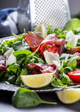 Dried beef bresaola. Salad bresaola arugula baby spinach tomatoes lime and cheese parmesan Royalty Free Stock Photography