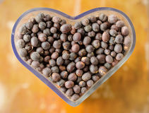 dried berries coffee beans on shaped heart bottle Stock Photos