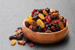 Dried  berries  and fruits in wooden bowl on black stone backgrou. Dried  berries and fruits in wooden bowl on black stone background Royalty Free Stock Image