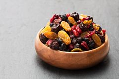 Dried  berries and  fruits in wooden bowl on black stone backgrou. Dried  berries and fruits in wooden bowl on black stone background Royalty Free Stock Photo