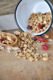 Dried berry and granola spilling on board Stock Photography