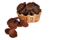 Dried black apricots on box. Dried black apricots on basket on white backgrounds royalty free stock photo