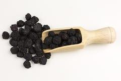 Dried aronia berries. Dried black aronia berries with wooden scoop  - aronia arbutifolia Royalty Free Stock Photos