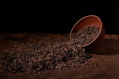 Dried black tea in clay bowl with sticks of cinnamon and a tea strainer isolated on black background. Dried black tea in clay bowl with sticks of cinnamon and a stock photography
