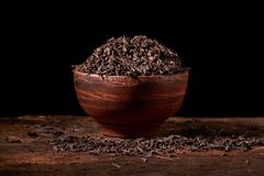 Dried black tea in clay bowl with sticks of cinnamon and a tea strainer isolated on black background. Dried black tea in clay bowl with sticks of cinnamon and a royalty free stock images