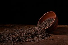 Dried black tea in clay bowl with sticks of cinnamon and a tea strainer isolated on black background. Dried black tea in clay bowl with sticks of cinnamon and a stock photos