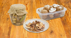 Dried boletus, pickled and fresh uncooked button mushrooms Stock Images