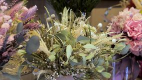 Dried bouquet with white statice flower, eucalyptus, chamomile and fern. Surrounded by bouquets with other flowers.