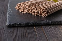 Dried buckwheat soba noodles on rustic wooden board stock photography