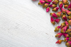 Dried buds of a tea rose on a  shabby wooden table. flat lay Stock Image
