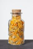 Dried calendula herb inside a glass jar. royalty free stock photography