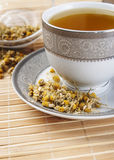 Dried camomile flowers surrounding fresh up of camomile tea. Close up photo Stock Images