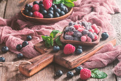Dried and candied fruits. And berries in wooden bowl with fresh raspberry and blueberry Royalty Free Stock Photos