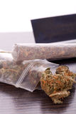 Dried Cannabis on Rolling Paper with Filter. Close up Dried Cannabis Leaves on a Resealable Cellophane Wrapper and a Rolling Paper with Filter on Top of the Stock Image