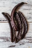 Dried Carob Pods. On wooden white background Stock Images
