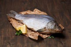 Dried carp with lemon and greens Stock Photo