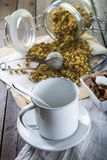 Dried chamomile flowers for brewing a camolile tea. And a vintage cup Royalty Free Stock Photography