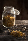 Dried chamomile flowers on a wood table. Dried chamomile flowers and tea-strainer on a wood table Royalty Free Stock Image