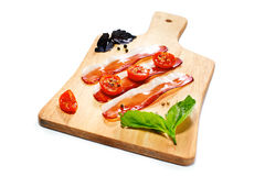 Dried cherry tomatoes with bacon served on carving board. Select Royalty Free Stock Images