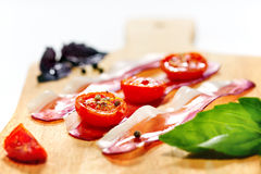 Dried cherry tomatoes with bacon served on cutting board. Stock Images