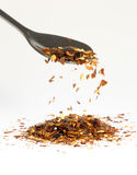 Dried Chili Pepper Falling from Tablespoon Stock Photo