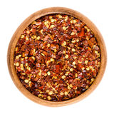 Dried chili pepper flakes in wooden bowl over white Royalty Free Stock Photography