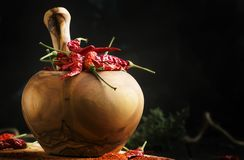Dried chili pepper and ground in wooden mortar, black kithen table, selective focus stock images