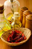 Dried chili peppers. Basket with dried chili peppers, olive oil and condiments Stock Images