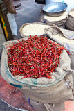 Dried chili peppers in bulk. Burlap bag of dried red chili peppers at an open air produce market in Surat, India Stock Photo