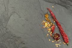 Dried chili peppers on dark slate. Strong spices for spicy foods. Decorate the kitchen. Royalty Free Stock Photography