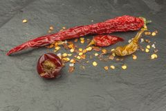Dried chili peppers on dark slate. Strong spices for spicy foods. Decorate the kitchen. Royalty Free Stock Image