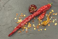 Dried chili peppers on dark slate. Strong spices for spicy foods. Decorate the kitchen. Stock Photo