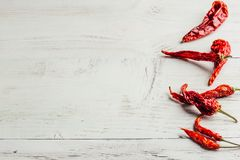 Dried chili peppers over wooden background stock image