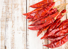 Dried chili peppers on wooden background Royalty Free Stock Images