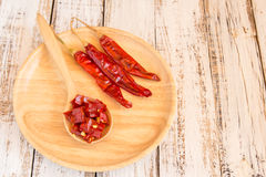 Dried chili peppers in wooden plate on wooden background Stock Photography