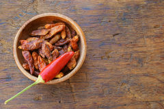 Dried chili pods in a wooden bowl. One whole chili pod on a bowl with dried chili on an old rustic wooden table with copy space Stock Photos
