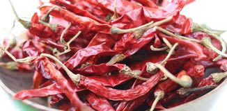Dried chilli. Red dried chilli is in the wooden basket,which was isolated on white background Stock Photo