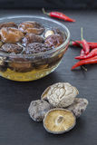 Dried Chinese mushroom and chilli on wooden background. Royalty Free Stock Photography