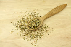 Dried chopped herbs in a wooden spoon. Texture stock photography