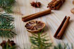 Dried citrus with cinnamon sticks, anise star on the wooden background decorated with Christmas tree branch. New Year composition Royalty Free Stock Photo