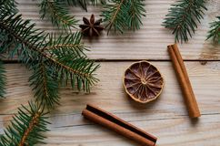 Dried citrus with cinnamon sticks, anise star on the wooden background decorated with Christmas tree branches. Traditional spices Royalty Free Stock Photos