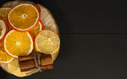 Dried citrus fruits on a black wooden surface, top view, Royalty Free Stock Photo