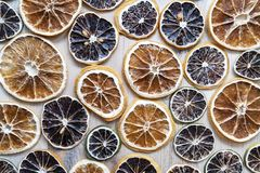 Dried citrus fruits lemon, lime and orange for decorating lie on a wooden textured table. Wallpaper. Top view. Close-up royalty free stock image