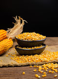 Dried corn in black ceramic bowl on wooden table Stock Image