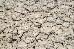 Dried and cracked earth soil from draught. Cracked terrain texture in summer from climate change and global warming effect royalty free stock photography
