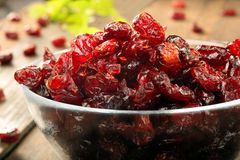 Dried cranberries in a glass bowl on wooden background Royalty Free Stock Photos
