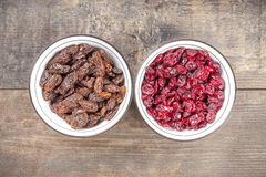 Dried cranberries and raisins in bowls on wooden background Stock Photos