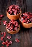 Dried cranberries in wooden bowls stock image