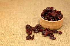 Dried cranberries in a wooden glass on a napkin. Dried cranberries in a wooden glass Royalty Free Stock Images