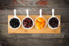 Dried cranberry, apricot, blueberries and cherries. Small ceramic dishes of dried cranberries, apricot, blueberries and cherries arranged in a row on a wooden Stock Photo